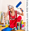 Repair home woman holding paint roller for wallpaper. 40674641