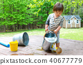 Toddler boy playing with a watering can 40677779