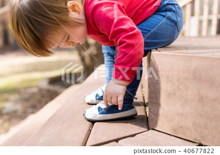 Happy toddler boy tying his sneakers 40677822