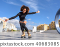 Black woman on roller skates riding outdoors on urban street 40683085