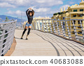 Afro hairstyle woman on roller skates riding outdoors on urban b 40683088