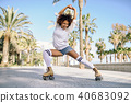 Black woman on roller skates rollerblading in beach promenade wi 40683092