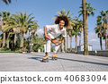 Black woman on roller skates rollerblading in beach promenade wi 40683094
