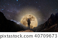 a man on the mountain with full moon at night 40709673