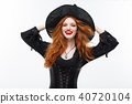 Halloween witch concept - Happy Halloween ginger hair Witch. Isolated on white background. 40720104