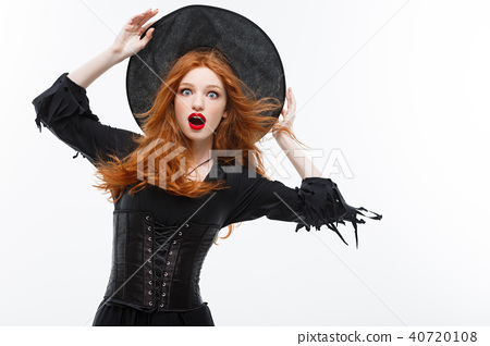 Halloween witch concept - Happy Halloween ginger hair Witch shocked of flying magic hat. Isolated on 40720108