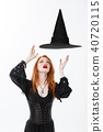 Halloween witch concept - Happy Halloween Sexy ginger hair Witch with magic hat flying over her head 40720115