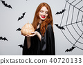 Portrait of beautiful caucasian witch holding pumpkin for celebrating Halloween. 40720133