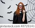 Halloween concept - Beautiful girls in black witch dresses holding party props. 40720141