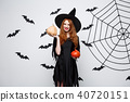 Portrait of beautiful caucasian witch holding pumpkin for celebrating Halloween. 40720151