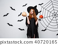 Portrait of beautiful caucasian witch holding pumpkin for celebrating Halloween. 40720165