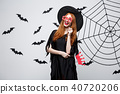 Halloween concept - Beautiful girls in black witch dresses holding party props. 40720206