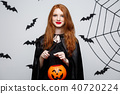 Portrait of beautiful caucasian witch holding orange pumpkin for celebrating Halloween. 40720224