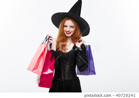 Halloween witch concept - Happy Halloween Witch smiling and holding colorful shopping bags on white 40720241