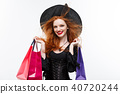 Halloween witch concept - Happy Halloween Witch smiling and holding colorful shopping bags on white 40720244