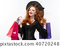 Halloween witch concept - Happy Halloween Witch smiling and holding colorful shopping bags on white 40720248