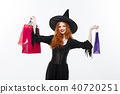 Halloween witch concept - Happy Halloween Witch smiling and holding colorful shopping bags on white 40720251
