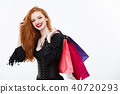 Halloween witch concept - Happy Halloween Witch smiling and holding colorful shopping bags on white 40720293