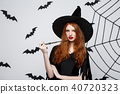 Halloween Concept - Beautiful Witch playing with magic stick on grey background. 40720323