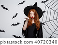 Halloween Concept - Beautiful Witch playing with magic stick on grey background. 40720340