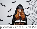 Halloween Concept - Beautiful dark priest casting spell with magic book on grey background. 40720359