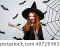 Halloween Concept - Beautiful Witch playing with magic stick on grey background. 40720363
