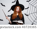 Halloween Concept - Beautiful Witch playing with magic stick on grey background. 40720365