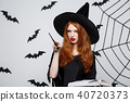 Halloween Concept - Beautiful Witch playing with magic stick on grey background. 40720373