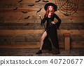 Halloween witch concept - Full-length Happy Halloween red hair Witch holding posing with magic 40720677