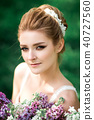Portrait of beauty bride in white dress. The bride is holding a wedding bouquet of lilacs. 40727560