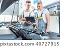 Experienced auto mechanic using a laptop for scanning engine error codes 40727915