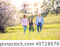 Senior couple with grandaughter outside in spring nature. 40728076