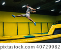 trampoline jumper performs acrobatic exercises on the trampoline 40729982