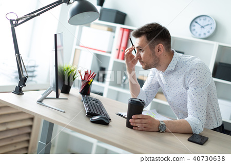 A young man is standing near a table in the office, holding a pencil and a glass of coffee. A young 40730638