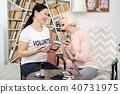 Jovial volunteer and senior woman having fun 40731975