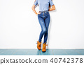 Young girl blue jeans brown shoes wall white. 40742378