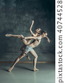 The young modern ballet dancers posing on gray studio background 40744528