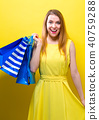 Happy young woman holding shopping bags 40759288