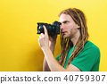 Young man holding a professional camera 40759307