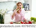 smiling woman tastes fresh celery in the kitchen 40760502