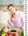 smiling woman tastes fresh celery in the kitchen 40760514