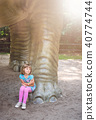 Cute little girl under huge diplodocus dinosaur 40774744