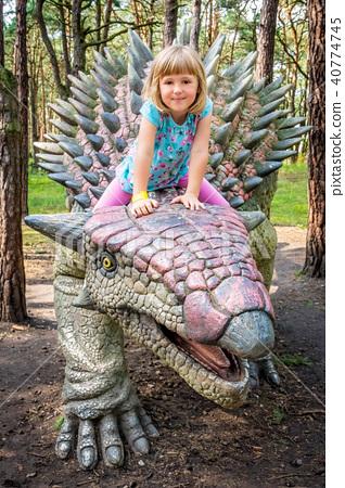 Cute little caucasian girl riding on Ankylosaurus dinosaur 40774745
