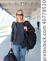 Portrait of young cheerful female traveler wearing casual clothes carrying heavy backpack and 40778530