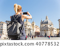 Female tourist with a fashinable vintage hipster backpack taking photo of Piazza del Popolo in Rome 40778532