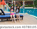 two young women friends enjoy with arms raised in swimming pool 40780105