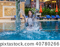 young woman splashing water in swimming pool 40780266