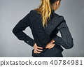woman stands by holding her waist, as if she is sick or uncomfortable 40784981
