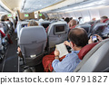 Interior of large commercial airplane with passengers on their seats during flight. 40791827