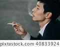 抽香煙的一個年輕商人 40833924